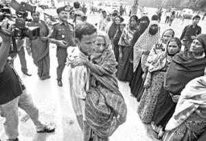 গাজীপুর উপনির্বাচনে �োট দিতে বয়োবৃদ্ধ এক নারীকে কোলে করে একটি কেন্দ্রে নিয়ে যাচ্ছেন তাঁর এক স্ব